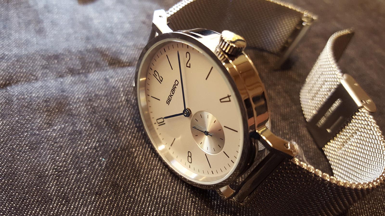 """da1218f94ad2dd 「SEKARO」というブランド名の入ったスモールセコンドのモデル。ブレス部分は""""ミラネーゼ""""と呼ばれるメッシュブレスレットで、細い青針と数字とバーを組み合わせた  ..."""