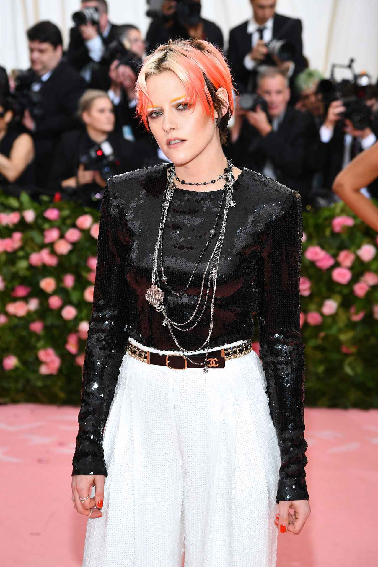 6626f2ad2e38a クリステンのこの日のスタイルは、全身シャネル(Chanel)。スパンコールが輝く黒のトップスにきらめく白のワイドパンツを合わせ、シャネルのネックレスとベルトで  ...