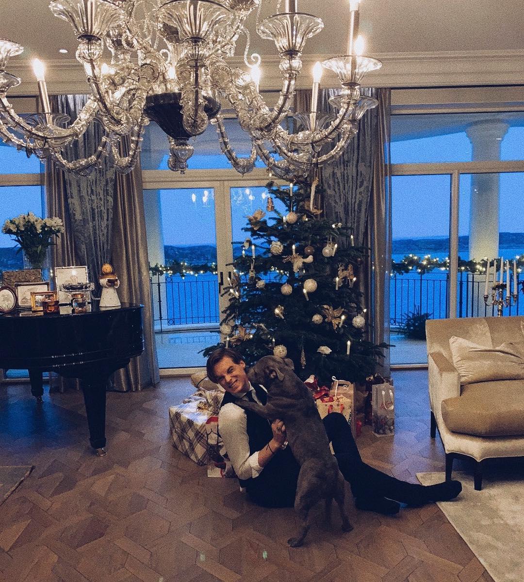14e231724e5 一面に海が見える窓に、シャンデリアやグランドピアノなど、ホテルのロビーと見まごうようなとてもゴージャスで巨大なリビング。寛いでワンちゃんと戯れている様子は、  ...